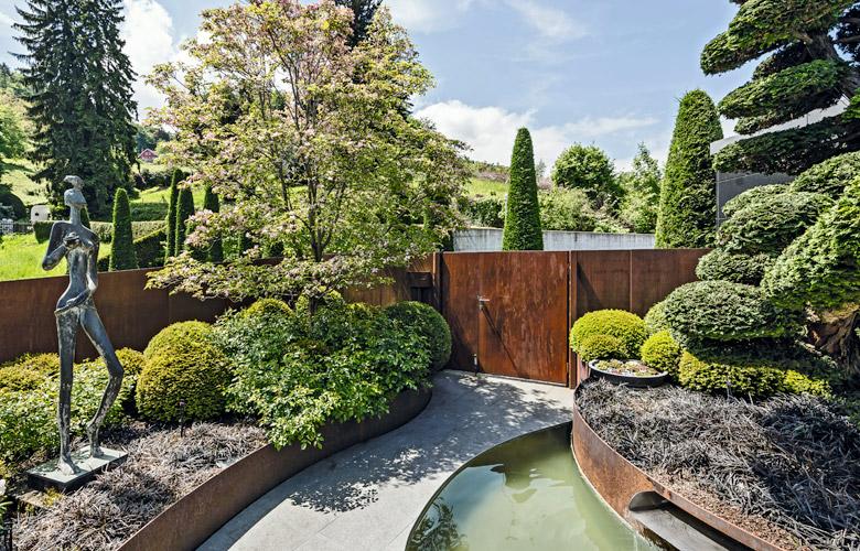 Ein Garten mit geschwungenen Linien und einer modernen Statue als Blickfang.