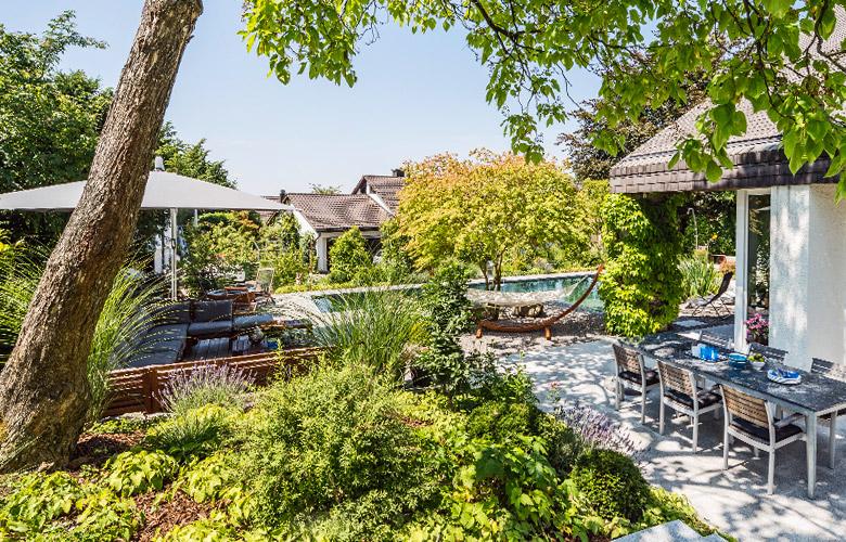 Ein Garten mit viel Grün, einem Pool und Möbeln, die Ferienfeeling verbreiten.