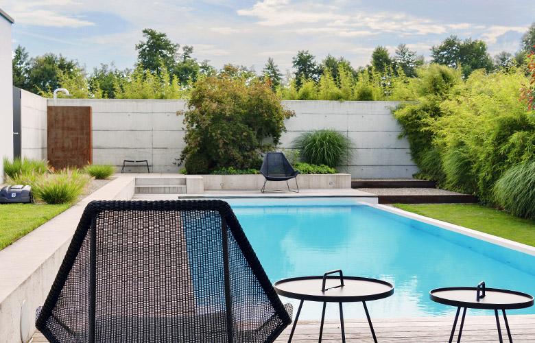 Ein grosser Pool mit geraden Linien und Betonelementen im Garten.