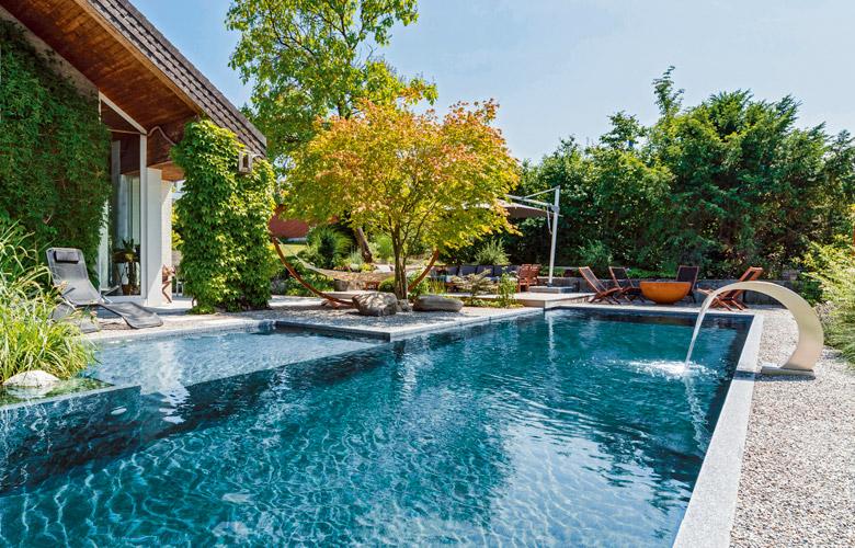 Ein moderner Pool mit Wasserfall-Element und einem Baum als Blickfang.