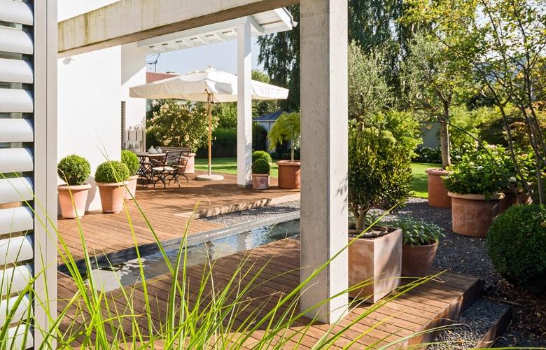 Ein schmales Wasserbecken bringt Atmosphäre in einen modernen Garten.